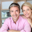 Cheerful couple leaning on kitchen counter — Foto de Stock