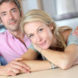 Cheerful couple leaning on kitchen counter — Stock Photo #13943174