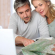 Mature couple planning vacation trip with map and laptop — Stock Photo #13943197