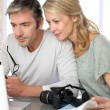 Stock Photo: Mature couple planning vacation trip with map and laptop