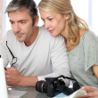 Mature couple planning vacation trip with map and laptop — Stock Photo #13943199