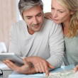 Mature couple planning vacation trip with map and laptop — Stock Photo #13943206