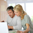 Mature couple planning vacation trip with map and laptop — Stock Photo #13943207