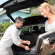 Couple putting suitcases in car trunk for a journey — Stock Photo #13943212