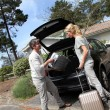 Couple putting suitcases in car trunk for a journey — Stock Photo #13943213