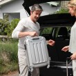 Stock Photo: Couple putting suitcases in car trunk for a journey