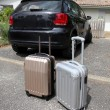 Closeup of suitcases set by a car in driveway — Stock Photo
