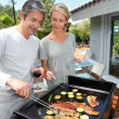 Couple in garden cooking meat on barbecue — Stock Photo #13943236