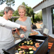 Couple in garden cooking meat on barbecue — Stock Photo #13943247