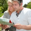 Couple on vacation looking at touristic map — Stock Photo #13943257