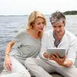 Couple sitting on boardwalk and using tablet — Stock Photo #13943289
