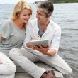 Couple sitting on boardwalk and using tablet — Stock Photo #13943291