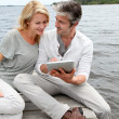 Couple sitting on boardwalk and using tablet — Stock Photo