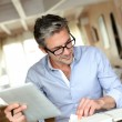 Handsome businessman with eyeglasses working from home — Stock Photo #13943317