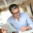 Stock Photo: Handsome businessmwith eyeglasses working from home