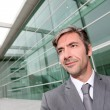 Portrait of businessman standing in front of modern building — Stockfoto