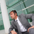 Businessman sitting in stairs in front of building — Stock Photo #13943377