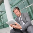 Businessman using electronic tablet in front of offices building — Stock Photo