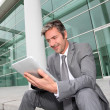 Stock Photo: Businessmusing electronic tablet in front of offices building