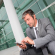 Stock Photo: Businessmusing mobile phone while seated in stairs