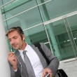 Businessman talking on mobile phone with handsfree headset — Stock Photo