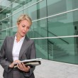 Mature businesswoman standing in front of modern building — Stock Photo #13943413