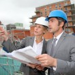 Construction engineers checking plan on building site — Stock Photo #13943476