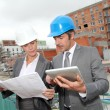 Construction engineers checking plan on building site — Stock Photo