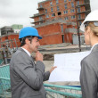 Construction engineers checking plans on building site — Stock Photo