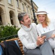 Trendy couple using electronic tablet on city bench — Stock Photo #13943504