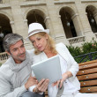 Trendy couple using electronic tablet on city bench — Stock Photo