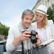 Happy tourists looking at pictures on camera screen — Stock Photo #13943547