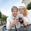Happy tourists looking at pictures on camera screen — Stock Photo #13943548