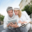 Couple visiting city with help of map and electronic tablet — Stock Photo #13943551
