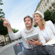 Couple visiting city with help of map and electronic tablet — Stock Photo