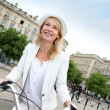 Cheerful middle aged woman riding bike in town — Stock Photo #13943557