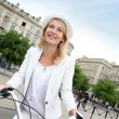 Cheerful middle aged woman riding bike in town — Stock Photo