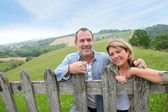 Senior couple leaning on fence in countryside — ストック写真