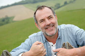 Portrait of smiling farmer leaning on fence — Stock Photo