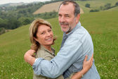 Portrait of happy senior couple in countryside — Stok fotoğraf