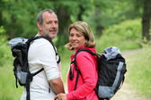 Portrait of smiling hikers in forest pathway — Stok fotoğraf