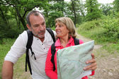Senior couple rambling in forest with map — Stock Photo