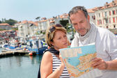 Senior couple in touristic area looking at map — Foto de Stock