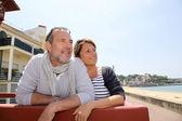 Casal sênior na estância balnear, olhando para a praia — Foto Stock