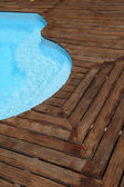 Closeup of swimming pool with wooden floor around — Stock Photo