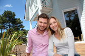 Portrait of smiling couple standing in front of house — Stok fotoğraf