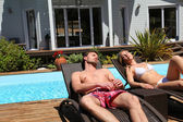 Couple suntanning in long chairs — Stock Photo