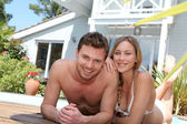 Happy young couple relaxing by pool — Stock Photo