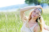 Beautiful blond woman in meadow with modern look — Stock Photo
