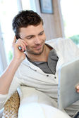 Man talking on the phone while using tablet — Stock Photo